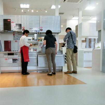 白い床に、白いシステムキッチンの説明を聞く中年の男女、赤色のエプロンをした男性の説明員がキッチンの説明をしています。