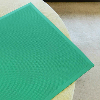 白い机の上に緑色の長方形のマットが置いてあります。