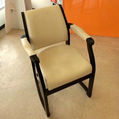 肌色の床のうえには濃茶色のフレームに肌色のビニルレザーを貼った椅子が置いてあります。