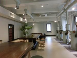 木目の床に木目の机と丸椅子が、数客。右に工場で使っていた機械が置いてあります