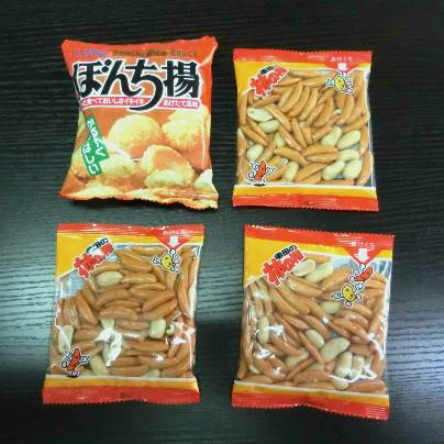 黒い机のうえでは左上にぼんち揚げの袋が1つ、右上と左下、右下には柿の種の袋が置いてあります。