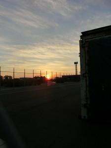 港に置いてあるコンテナの左側に新年の初日の出が上がって行く様子です。