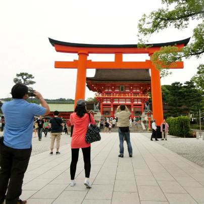 伏見稲荷大社の鳥居の前で写真を撮る人たちが写っています。