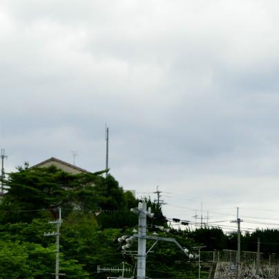 写真の下側に樹木と民家、空は雲に覆われています。