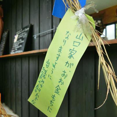 薄い緑色の短冊に青いインクで「山口家がおお金もちになりますように」と書いてあります。