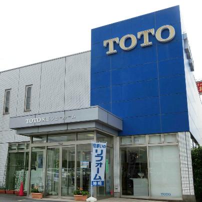 TOTOの青い看板の前、正面入り口の右側にリフォーム神崎と書いた幟旗が立っています