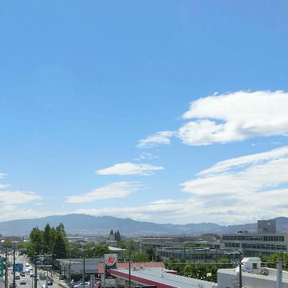遠くに山が見えて、真っ青な空がその上に広がり、右側には真っ白い雲が浮かんでいます。