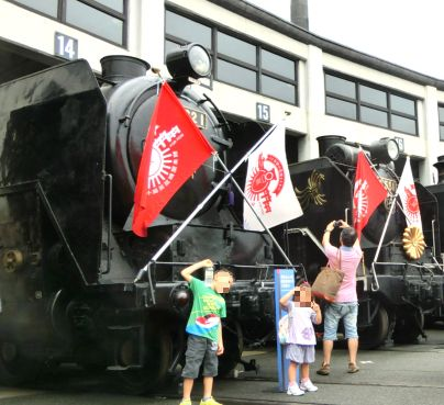蒸気機関車の前で写真を撮る子供たち