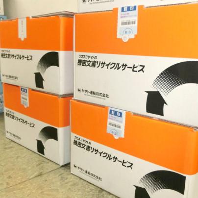 オレンジと白のツートーンの段ボール箱が4箱積んであります。