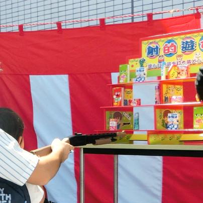 右側にお菓子の的、左側にはおもちゃのライフルを持った親子連れが撃っているところです