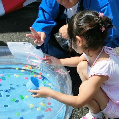 透明のビニルプールにスーパーボールをたくさん浮かべています。小さな女のお子さんがポイをもって救っています。
