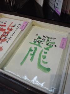 筆で緑の文字で龍と大きく書いた葉書に、A HAPPY NEW YEAR 2012 と書いてある年賀状