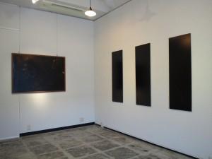 白い壁の展示場の角を写しています。左の壁には横長の写真が一枚、土に芽生える若葉を写しています。右の壁には幟のような縦長の黒い写真が3枚。