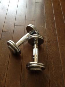 茶色いフローリングの床に銀色のダンベルが2つ置いてあります