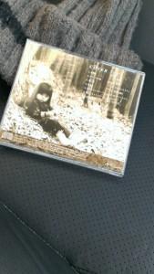 セピア色の写真に幼子が枯れ木を敷いた公演らしき場所に座っている写真