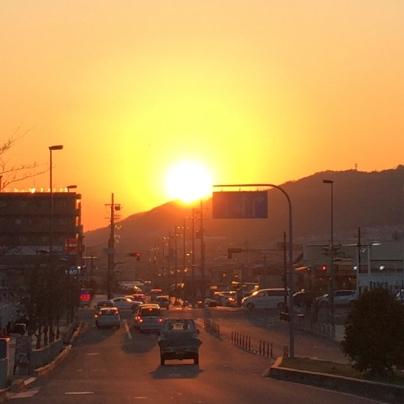 道路の向こうに山裾があり、そこに太陽が沈もうとしています。
