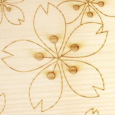 白い高野槇の板に、桜の花を模した柄で、彫り河口してあります