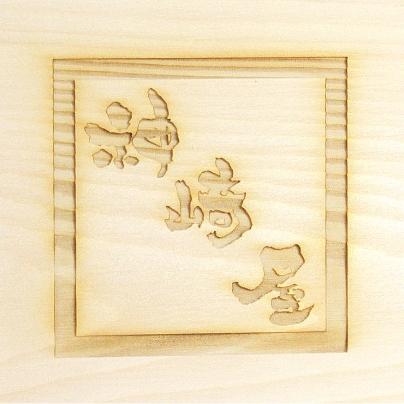 白い高野槇の板に、茶色い文字で神崎屋、その神崎屋を真四角で囲ってあります。