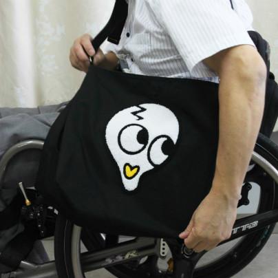車いすに座った男性が黒いトートバッグを肩にかけています。バッグの表面には白い髑髏をデフォルメしたキャラクターが一面に描かれています。