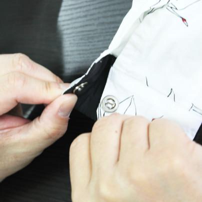 シャツの袖口ボタンである磁石をとめようとしています
