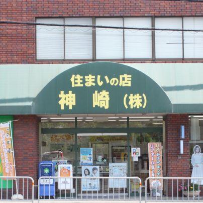 緑色のテントに黄色い文字で住まいの店神崎(株)と書いてあります