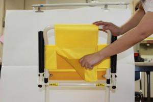 黄色いシャワーチェアを左手で支え、シートを右手でめくっています