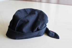 白い机の上に黒いバンダナを帽子状にくくった akko バンダナ帽 が、載っています