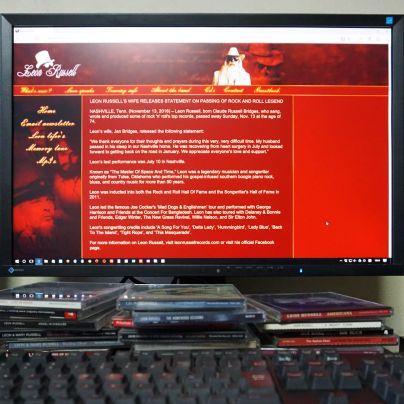 パソコンモニターに濃い臙脂色の背景、そこに英語でレオン・ラッセルの妻がレオンの氏を発表しています