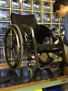 テーブルの上に車椅子を載せて修理中。