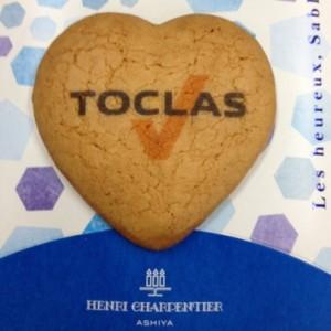 青と薄紫のアンリシャルパンティエのパッケージにハート型のサブレが1つ載っています。サブレの中央にはTOCLASのロゴがあり。
