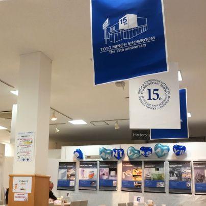 天井から白色と青色の旗が垂れ下がっていて、奥の壁にはTOTOさんの歴史を記したパネルが並んでいます