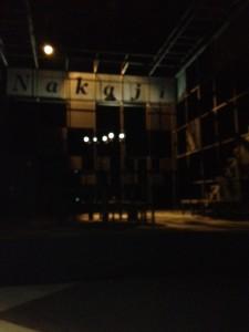 舞台の上にフレームで会社の事務所、ローマ字で「nakaji」と書いた看板があがっています