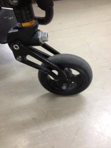 事務所のしろい床に、黒い車椅子のキャスター(前輪)がアップで映っています。