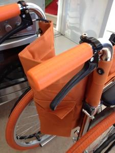 オレンジ色の車椅子の押し手の部分をアップにしています。