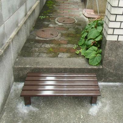 コンクリートの通路と住宅敷地との境界に茶色いアルミ製の横長の踏み段を設置しています。