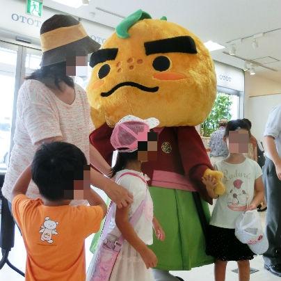 子供達に囲まれた柚子の侍を模したキャラクターが立っています。
