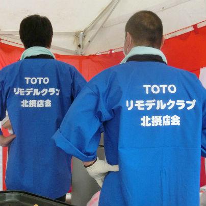 男子社員が2人背中を向けて立っています。青いはっぴに白い文字でTOTOリモデルクラブ北摂店会