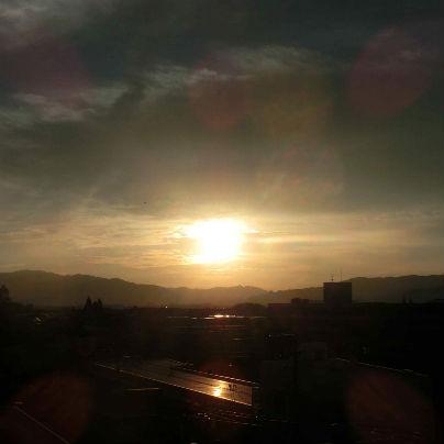 六甲の山稜にオレンジ色の夕陽が沈んでゆく様子が映っています。