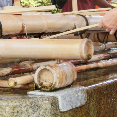石のうえに水盤が据え付けらていて、柄杓で女子が水をくんでいます。