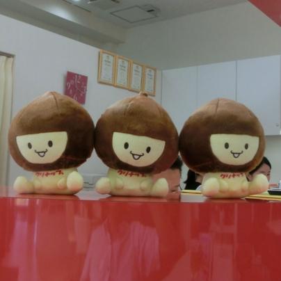 栗の頭に笑顔の子供ふうのキャラが赤いカウンターの上に三体並んで座っています。