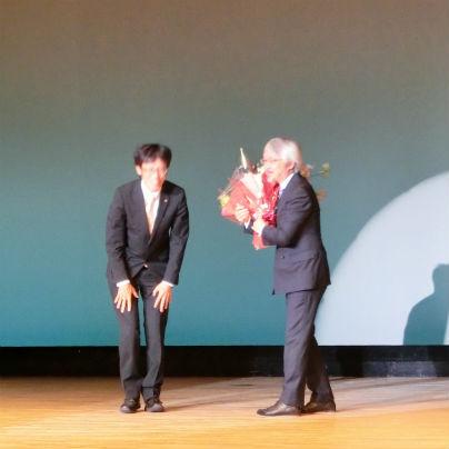 舞台の上で濃紺の背広を着た男が左、右にグレーの背広をきた銀髪の小阪裕司氏