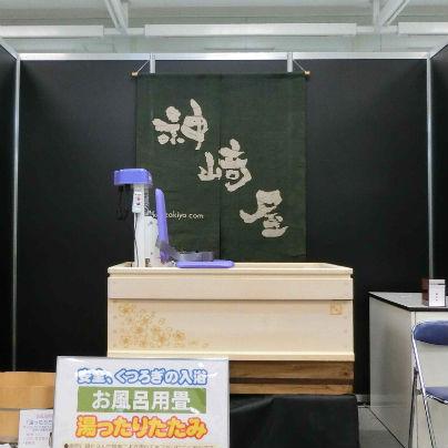 神崎屋の暖簾の前に白い木製介護浴槽を置き、その中に介護リフトを1台展示しています。