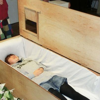 棺桶のなかに普段着姿の若い女性が横たわっています。