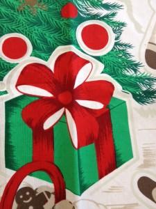 白地のテーブルクロスには、緑色の箱に赤いリボンを掛けた絵が描かれています。