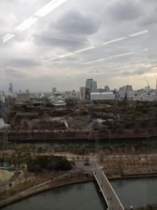 冬景色の大阪城公園のなかほどに緑色の屋根をした大阪城が写っています。