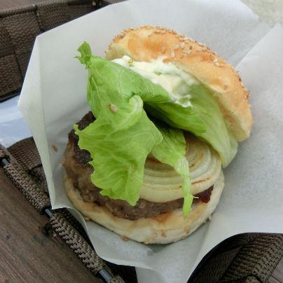 茶色い籐のバスケットに白い紙、その上にハンバーガーが載っています。