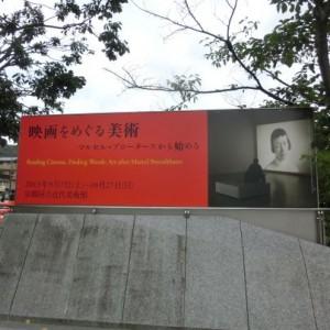 横長の看板は左側三分の二に「映画をめぐる美術」の文字、右皮に英側で女性を映しているスクリーン