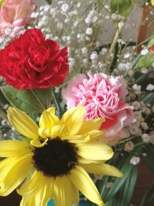 黄色い向日葵の左後ろに赤いカーネーション、右後ろにはピンクのカーネーション