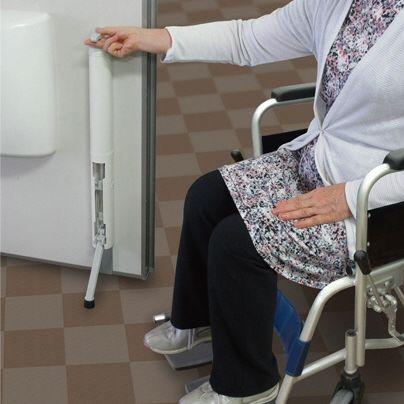 画面の右側に車椅子に乗る年嵩の女性。左側は、開いた白いドア。どのドアに内側は、縦に長いドアストッパーがついています。