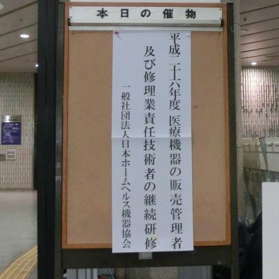 本日の催物と書いたボードに白い貼り紙、平成二十六年度 医療機器の販売・賃貸管理者及び修理業責任技術者継続研修 一般社団法人日本ホームヘルス機器協会